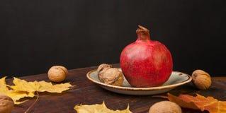 Granaatappel op houten achtergrond met bladeren Stock Afbeeldingen
