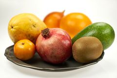 Granaatappel, papaja, mango - een reeks exotische vruchten op metaalplaten geïsoleerde studio stock fotografie