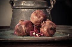 Granaatappelfruit op roestig dienblad en een bloem Stock Foto