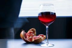 Granaatappelsap in een glas en sommige stukken van granaatappel op een zwarte achtergrond Vitaminen en Mineralen stock afbeelding