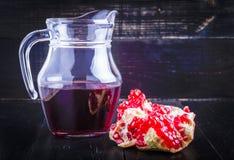 Granaatappelsap en granaatappeldelen Stock Fotografie