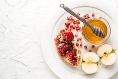 Granaatappelzaden, appelen met honing op een ceramische plaat Stock Foto