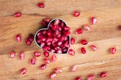 Granaatappelzaden in de hart-vormige vorm op de houten raad Royalty-vrije Stock Fotografie