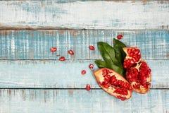Granada cortada madura dulce en la madera azul con las hojas y las semillas Imagen de archivo