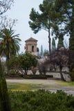 GRANADA, ESPAÑA - 10 DE FEBRERO DE 2015: Una vista a una torre con las banderas en día de niebla lluvioso en la yarda de Alhambra Foto de archivo