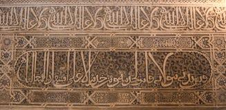 GRANADA, ESPANHA - 10 DE FEVEREIRO DE 2015: Uma opinião do close-up à caligrafia decorou detalhes de uma arcada no palácio de Alh Foto de Stock