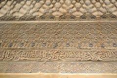 GRANADA, ESPANHA - 10 DE FEVEREIRO DE 2015: Uma opinião do close-up à caligrafia decorou detalhes de uma parede no palácio de Alh Imagens de Stock Royalty Free