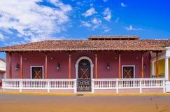GRANADA, NIKARAGUA, MAJ, 14, 2018: Plenerowy widok fasadowi budynki z menchii ścianą, drewnianym drzwi i dachem w wspaniałym, fotografia royalty free