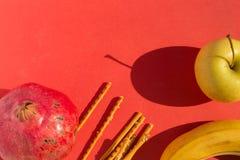 Granada roja grande, manzana de oro, plátano fresco y palillos salados Imagenes de archivo