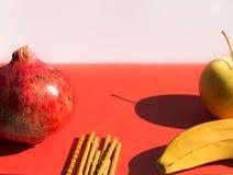 Granada roja grande, manzana de oro, plátano fresco y palillos salados Imagen de archivo libre de regalías