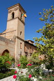 Granada, Spain: Alhambra Bell Tower & Gardens. A pink sandstone medieval bell tower overlooks rose gardens at the historic Alhambra in Granada, Spain Stock Photography