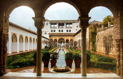 GRANADA, SPAIN - FEBRUARY 10, 2015: An archway to patio with fountains and cutted brushes at Generalife Gardens of Alhambra palace. Granada, Andalusia, Spain Stock Images