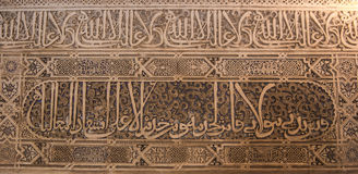 GRANADA, SPAIN - FEBRUARY 10, 2015: A close-up view to calligraphy decorated details of an archway at palace of Alhambra Stock Photo