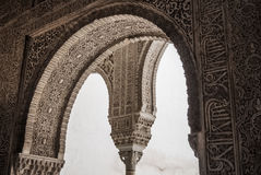 GRANADA, SPAIN - FEBRUARY 10, 2015: A close-up view to calligraphy decorated details of an archway at palace of Alhambra Royalty Free Stock Images
