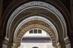 GRANADA, SPAIN - FEBRUARY 10, 2015: A close-up view to calligraphy decorated details of an archway at palace of Alhambra Royalty Free Stock Image