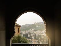 GRANADA, SPANIEN - 10. FEBRUAR 2015: Eine Ansicht zu den alten weißen Häusern von Granada über dem Hügel durch ein verziertes Fen Stockfotos