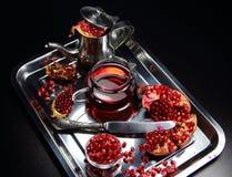 Granada y jugo garanotovy en un plato del metal con una tetera Foto de archivo