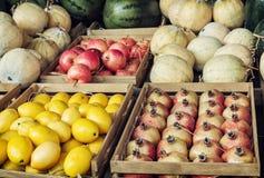 Granadas, limones, melones y manzanas en los envases de madera - m Imagen de archivo