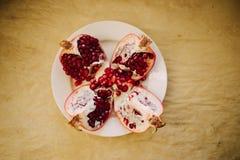 Granadas maduras rojas en una placa blanca, fondo del papel del arte, visión superior de Cutted imágenes de archivo libres de regalías