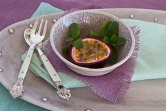 Granadilla with mint and spoon and fork Stock Photos