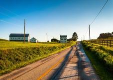 Granai e casa lungo una strada campestre nella contea di York rurale, PA immagini stock