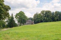 Granaio armato in legno storico della vecchia casa dell'azienda agricola con il pascolo verde del prato Fotografia Stock Libera da Diritti