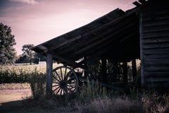 Granaio del paese anziano, con un aratro d'annata sotto Immagini Stock