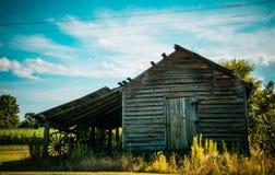 Granaio del paese anziano, con un aratro d'annata sotto Fotografia Stock Libera da Diritti