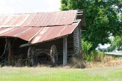 Granaio del paese anziano, con un aratro d'annata sotto Fotografie Stock Libere da Diritti