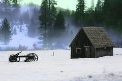 Granaio e vecchio vagone di legno nella neve Immagine Stock Libera da Diritti
