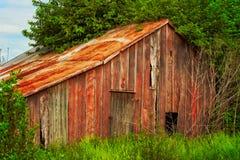 Granaio rosso arrugginito dilapidato Fotografia Stock