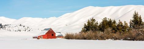 Granaio rosso degli agricoltori in un campo di neve e delle montagne Immagine Stock