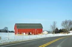Granaio rosso, inverno, strada campestre immagini stock libere da diritti