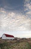 Granaio sotto un cielo nuvoloso Immagini Stock