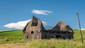 Granaio sprofondante nel campo di un agricoltore Fotografie Stock Libere da Diritti