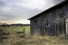 Granaio stagionato alla destra con il recinto Fotografie Stock