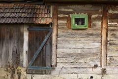 Granaio tradizionale con la porta di legno e la piccola finestra Fotografia Stock Libera da Diritti