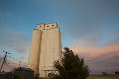 Granary Against an Evening Sky in the Texas Panhandle. A tall and white granary along the railroad tracks in the Texas panhandle at dusk stock photo