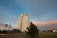 Granary Against an Evening Sky in the Texas Panhandle. A tall and white granary along the railroad tracks in the Texas panhandle at dusk stock image