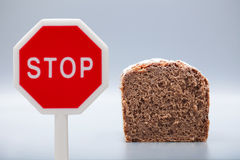 Granary Bread on gray background with stop sign Royalty Free Stock Photo