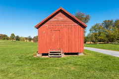 Granary. A bright reddish wooden granary on the green grass with the blue sky in the background Stock Photo