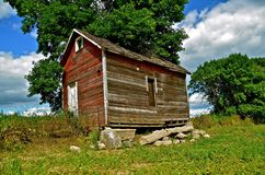 Granary on Crumbling Foundation. An old granary rests on a crumbling foundation in the the pasture Stock Images