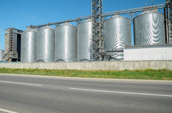 Granary near the road. Steel barns behind fence Stock Photography