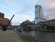 The granary wharf area in leeds with an old crane and boats on the canal with city center buildings and historic waterside. Achitecture royalty free stock photos