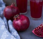 Granatäpfel und Granatapfelsaft in einem Glas auf einer grauen Tischdecke Das Konzept einer gesunden Diät und der Diät Selektiver Stockbilder