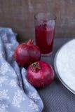 Granatäpfel und Granatapfelsaft in einem Glas auf einer grauen Tischdecke Das Konzept einer gesunden Diät und der Diät Selektiver Stockbild