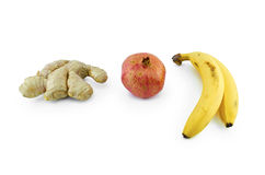 Granatäpple, ingefära och bananer som isoleras på vit Arkivfoton