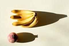 Granatäpple och en grupp av bananer mogen röd saftig granatäpple och en mogen grupp av bananer royaltyfri fotografi