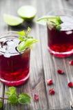 Granatäpplecoctail med den granatäpplefrö, limefrukt och mintkaramellen Alkoholist och icke-alkoholist Arkivfoto