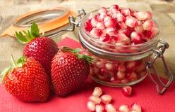 Granatäpplefrö och jordgubbar Arkivfoton